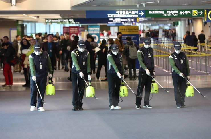Sanitation workers at Incheon International Airport disinfect the Arrival Hall as a part of efforts to stop the spread of a new type of coronavirus here, Tuesday. /Yonhap
