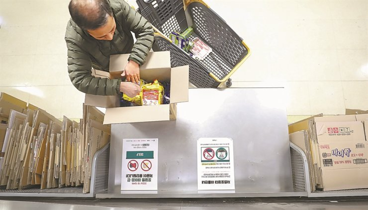 A customer puts groceries into a cardboard box at a Seoul-based discount store, Wednesday, when the four major retailers stopped providing packaging tape and strings. / Yonhap