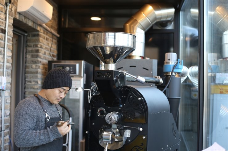 Joseph Park, a North Korean defector turned coffee shop owner, roasts coffee beans at one of his cafes in Seoul. Park has aided fellow defectors to get back on their feet through free barista lessons. Courtesy of Joseph Park