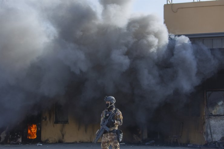 An Iraqi soldier stands guard in front of smoke rising from a fire set by pro-Iranian militiamen and their supporters in the U.S. embassy compound , in Baghdad, Iraq, Wednesday, Jan. 1, 2020. AP
