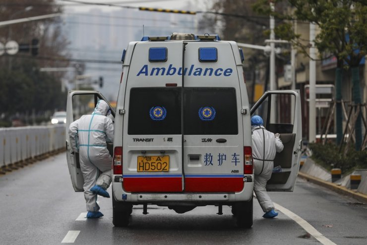In this Sunday, Jan. 26, 2020, photo, ambulance crew members in protective gear get into their ambulance in Wuhan in central China's Hubei Province. A new viral illness being watched with a wary eye around the globe accelerated its spread in China. AP