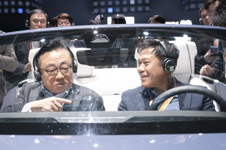 Koh Dong-jin, left, president of Samsung Electronics' mobile business, talks with SK Telecom CEO Park Jung-ho while sitting in Samsung's 2020 Digital Cockpit automotive electronics platform at the Consumer Electronics Show in Las Vegas, Wednesday (KST). / Courtesy of Samsung Electronics