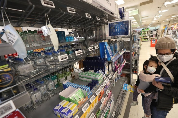 Customers wearing masks shop at a discount store in Seoul, Tuesday. / Yonhap