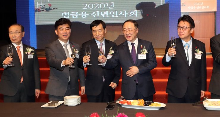 Finance Minster Hong Nam-ki, second from right, Bank of Korea Governor Lee Ju-yeol, center, and other financial leaders raise their glasses at a New Year's celebration event at Hotel Shilla Seoul, Jan. 3. Yonhap