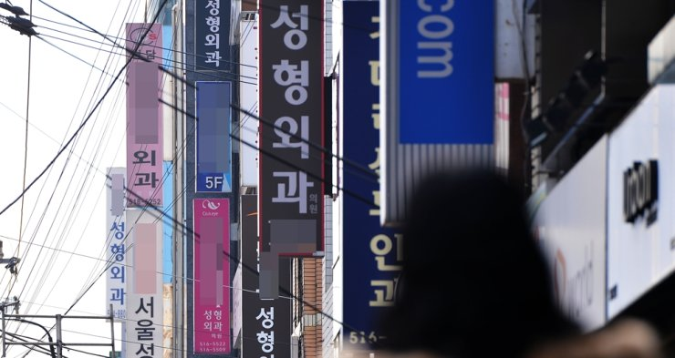 A multitude of billboards for cosmetic surgery clinics line a street in Apgujeong, southern Seoul in this 2012 file photo. / Korea Times file