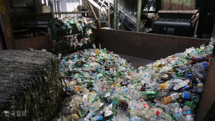 PET bottles are processed at a local recycling center in Gyeonggi Province. Seoul's new recycling rules will force residents to collect transparent PET bottles for recycling from Feb. 1./ Korea Times file