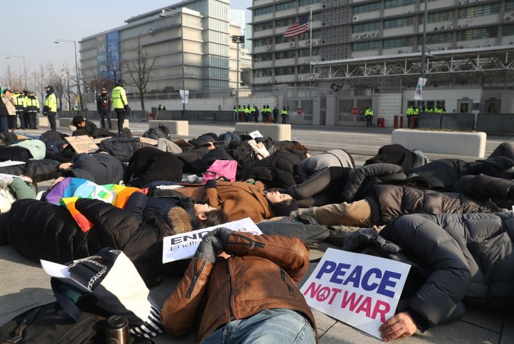 Members of activists group stage a performance in Gwanghwamun Square near the U.S. Embassy in Seoul, Friday, to denounce the U.S. request for Korea to send a naval unit to the Strait of Hormuz after tensions between Iran and the U.S. escalated. / Yonhap