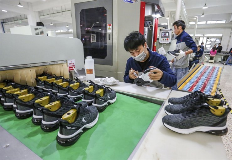 In this Jan. 3, 2020, photo, workers make sneakers in a factory in Jinjiang city in southeastern China's Fujian province. China's economic growth sank to a new multi-decade low of 6.1 percent in 2019 as consumer demand weakened and Beijing fought a trade war with Washington. AP