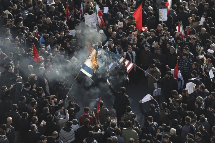 Mourners burn flags of the U.S. and Israel during a funeral ceremony for Iranian Gen. Qassem Soleimani and his comrades, who were killed in Iraq in a U.S. drone strike on Friday, at the Enqelab-e-Eslami (Islamic Revolution) square in Tehran, Iran, Monday. AP-Yonhap