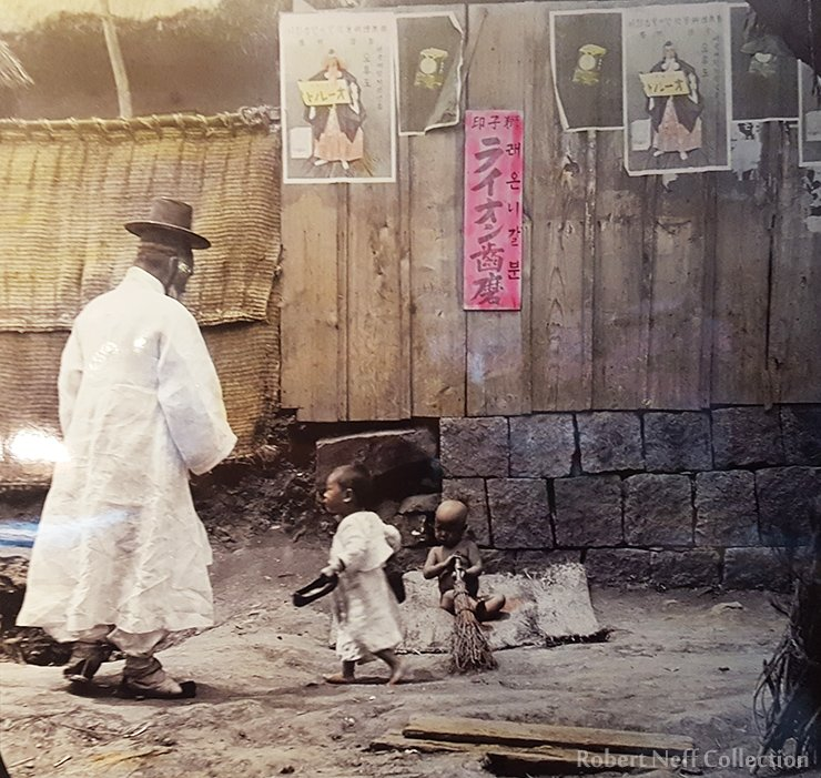 An elderly man and some children. One of the posters on the wall is an advertisement for Lion Toothpaste. The Bozoky Dezso Exhibit at the Seoul Museum of History Museum. Robert Neff, November 2019.