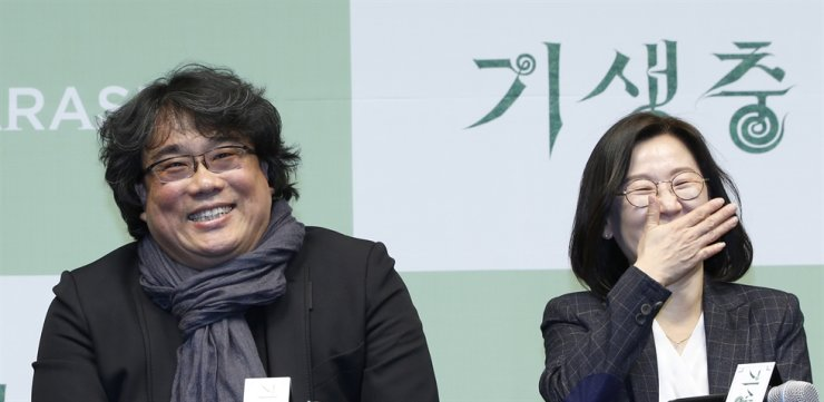 Korean director Bong Joon-ho (L) and producer Kwak Sin-ae (R) smile during a press conference for the movie of Parasite in Seoul, Feb. 19, 2020. EPA