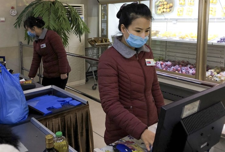 Supermarket assistants wear face masks at the Munsu-dong diplomatic compound amid the outbreak of the 2019-nCoV coronavirus. Yevgeny Agoshkov/TASS/