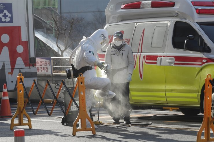 An emergency 119 staff member sprays disinfectant on himself after driving the country's 22nd confirmed coronavirus patient to Chosun University Hospital in Gwangju, Thursday. / Yonhap