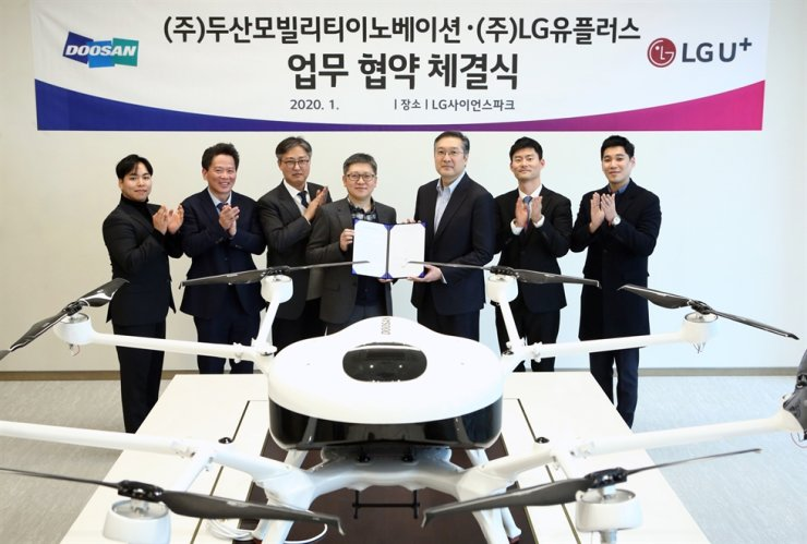 Cho Won-seok, fourth from left, head of new business unit at LG Uplus, poses with Lee Doo-soon, third from right, CEO of Doosan Mobility Innovation, after signing an MOU at LG Science Park in Seoul in this photo provided by LG, Sunday. / Courtesy of LG Uplus