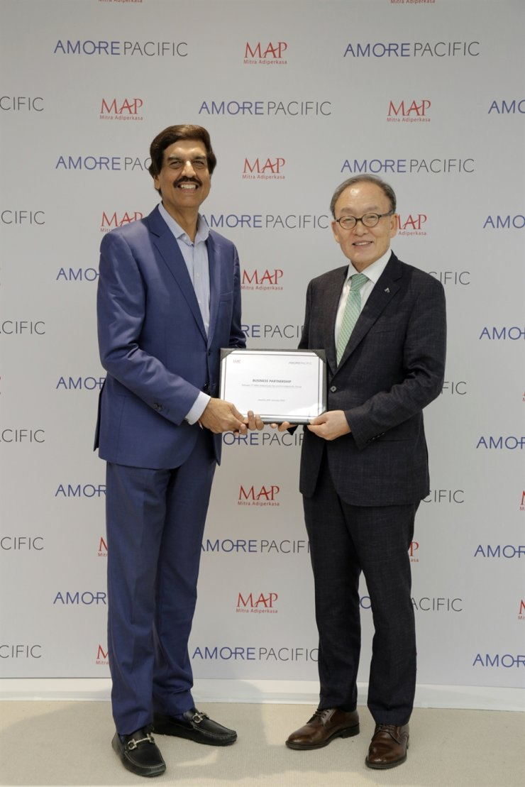 AmorePacific President Bae Dong-hyun, right, shakes hands with MAP Group CEO Virendra Sharma after signing a business partnership at the MAP headquarters in Jakarta, Indonesia, last Wednesday. / Courtesy of AmorePacific