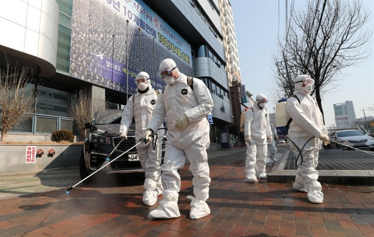 Officials from a public health center in Daegu disinfect streets near a church, Thursday, as dozens of the members of the church were confirmed to have been infected with the new coronavirus. / Yonhap