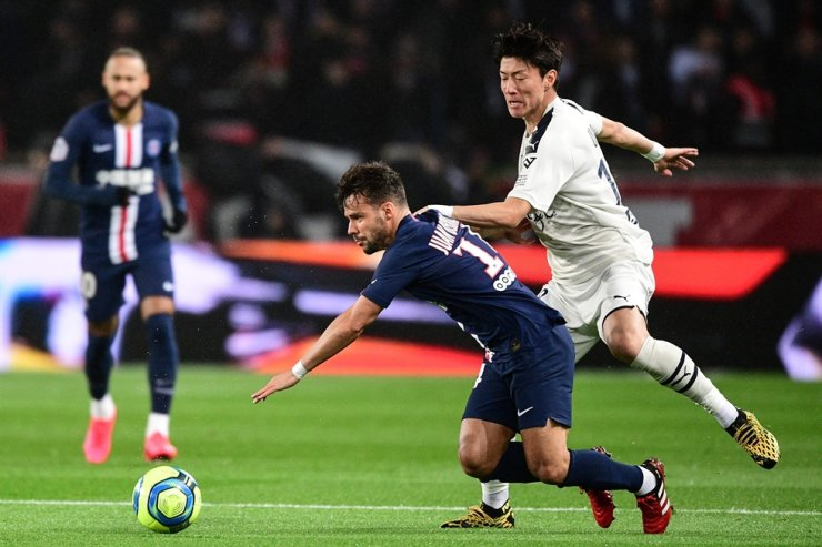 Paris Saint-Germain's Spanish defender Juan Bernat, center, vies with Bordeaux's South Korean forward Hwang Ui-Jo, right, during the French L1 football match between Paris Saint-Germain and Girondins de Bordeaux at the Parc des Princes stadium in Paris, Sunday. /AFP-Yonhap
