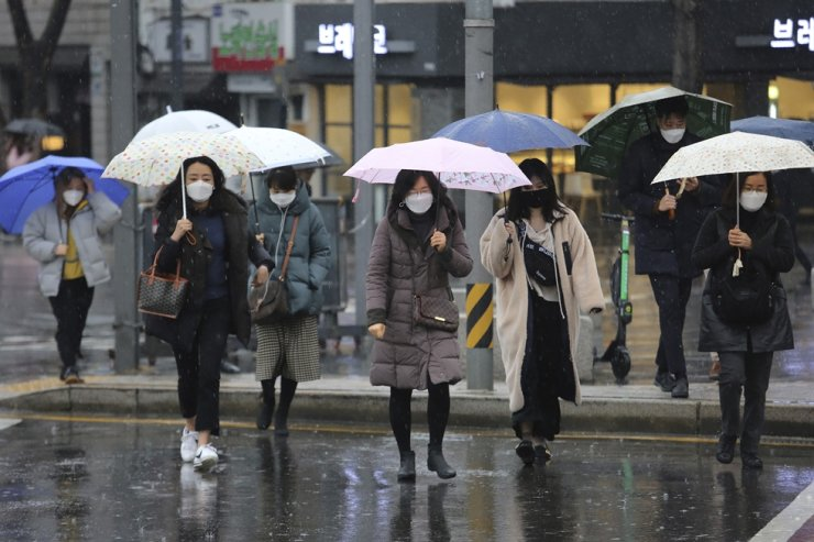 People wearing face masks contend with a rainy Tuesday in Seoul. AP