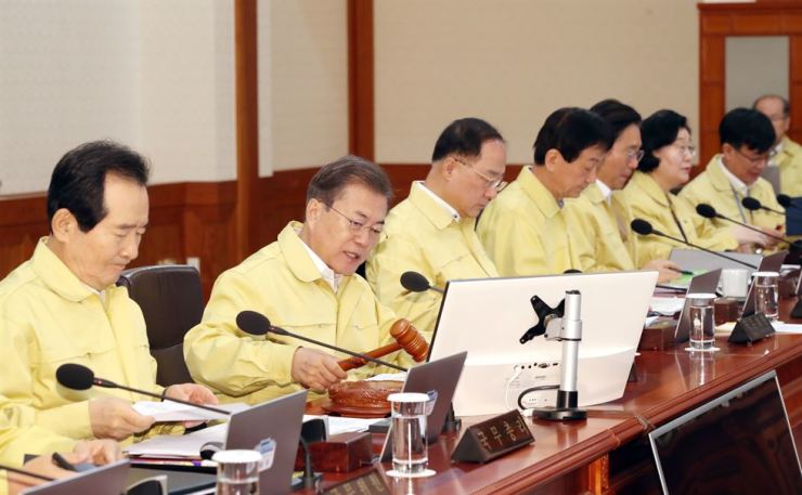 President Moon Jae-in, second from left, presides over a Cabinet meeting at Cheong Wa Dae, Tuesday, to discuss measures to contain the coronavirus outbreak. Yonhap