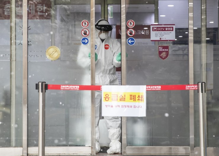 A health official in protective gear closes the door of the emergency room of Korea University Medical Center in Anam-dong, Seoul, Sunday. Yonhap
