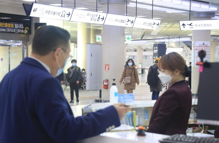 People wear face masks at Jeju International Airport, Feb. 21. Yonhap