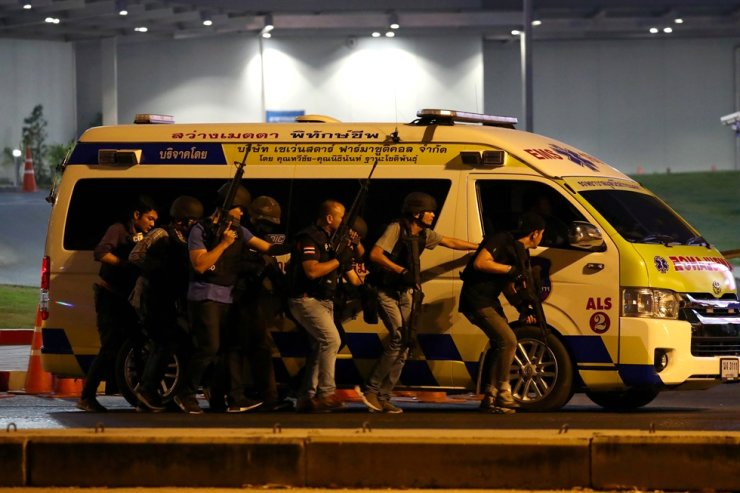 Thai security forces take cover behind an ambulance as they chase a shooter hidden in a shopping mall after a mass shooting in front of the Terminal 21, in Nakhon Ratchasima, Thailand, Feb. 9, 2020. Reuters