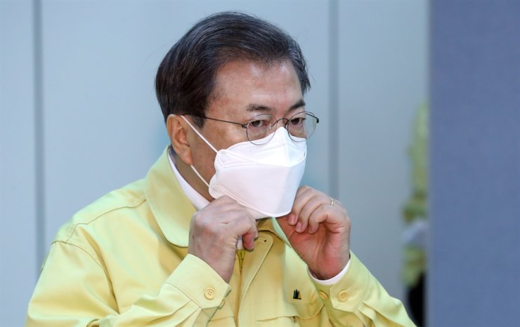 President Moon Jae-in adjusts his mask during his meeting with small merchants in Taegu, Korea's epicenter of the coronavirus epidemic. Yonhap