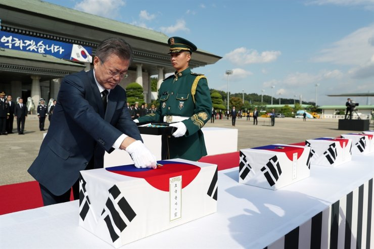 President Moon Jae-in puts war medals on the remains of 64 South Korean soldiers killed in North Korea during the 1950-53 Korean War, after they arrived at Seoul Air Base in Seongnam, Gyeonggi Province, Oct. 1, 2018, from Hawaii. The remains were found during a joint excavation project between United States and North Korea and later identified to be South Koreans through joint work by the U.S. and South Korea. Korea Times file