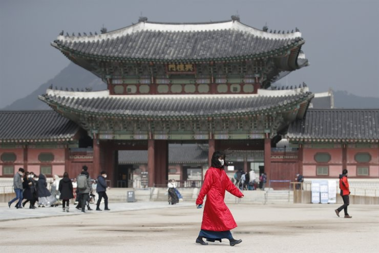 A woman wearing a face mask walks at the Gyeongbok Palace in Seoul, Saturday, Feb. 22, 2020. AP