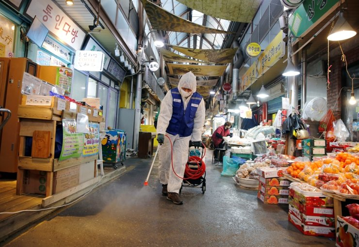 An employee from a disinfection service company sprays disinfectant at a traditional market in Seoul, Feb. 7. Reuters