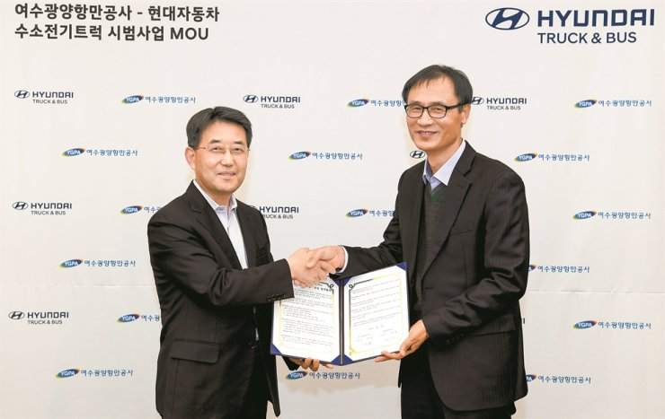 Lee In-cheol, left, head of Hyundai Motor's commercial business division, shakes hands with Gil In-hwan, head of management of Yeosu Gwangyang Port Authority, after signing a MOU to develop a hydrogen truck ecosystem, Friday. / Courtesy of Hyundai Motor