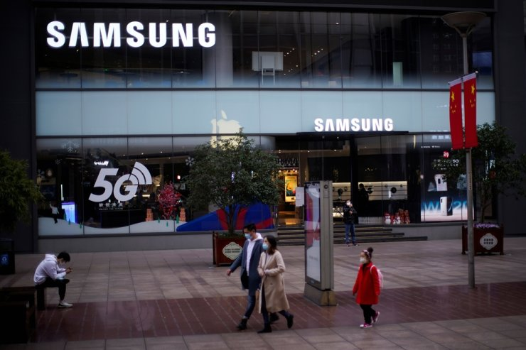 People wears masks in front a Samsung Store at a main shopping area as the country is hit by an outbreak of the new coronavirus in downtown Shanghai, China, Feb. 21. Reuters-Yonhap