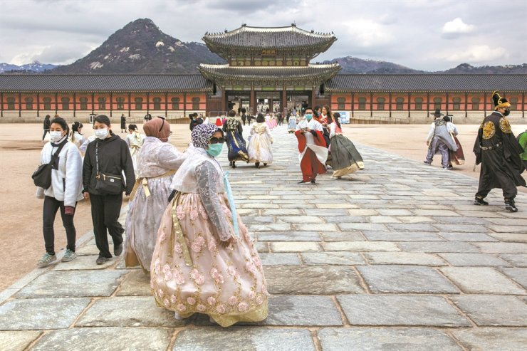 Foreign tourists wearing masks tour Gyeongbokgung Palace in Seoul, Wednesday. The number of COVID-19 infections here surpassed 1,000, Wednesday, 37 days after the first case was reported. /Korea Times photo by Shim Hyun-chul