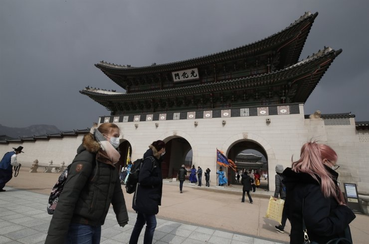 Visitors wearing face masks walk near the Gwanghwamun in central Seou, Saturday, Feb. 22, 2020. /AP