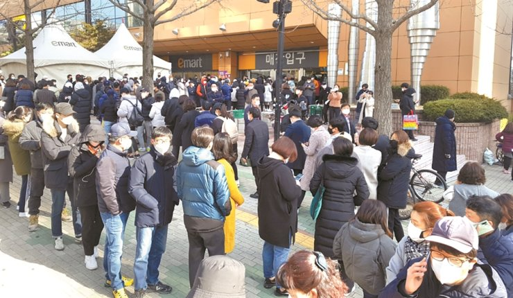 Citizens in Daegu wait in long lines to buy facial masks in front of E-mart's Manchon branch, Monday, as the number of coronavirus patients has been skyrocketing in the region. Yonhap