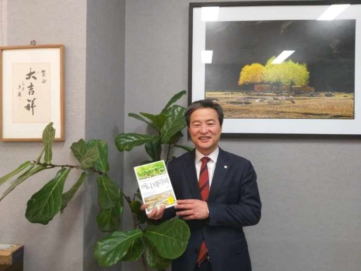 Cho Sung-mok, head of the Korea Research Institute for Financial Inclusion, poses with his book 'Money Therapy' at his office in southern Seoul. / Courtesy of Cho Sung-mok