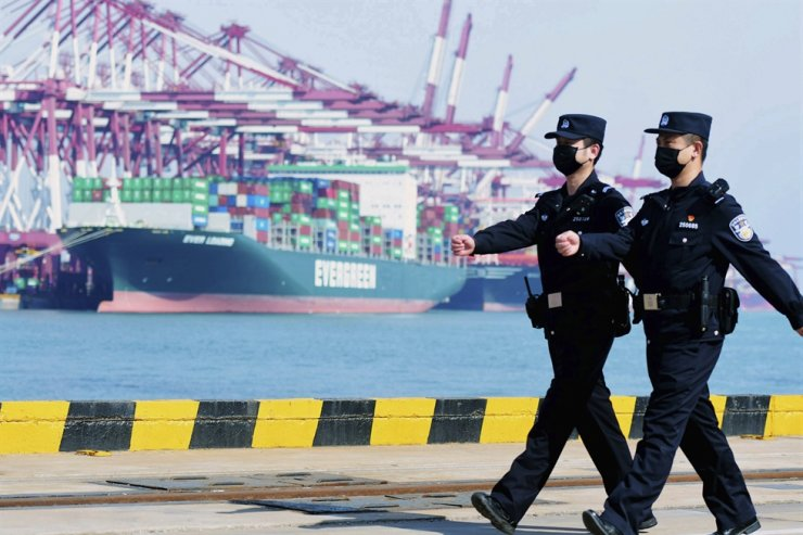 In this Feb. 19, 2020, photo, police officers wearing face masks patrol at a container port in Qingdao in eastern China's Shandong Province. AP