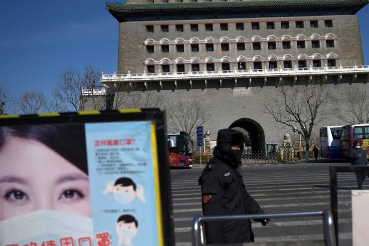 A security guard wearing a face mask walks past a poster promoting mask-wearing near the Qianmen pedestrian street, following an outbreak of the novel coronavirus in the country, in Beijing, Feb. 18, 2020. Reuters
