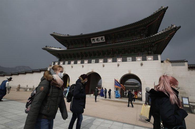 Visitors wearing face masks walk near the Gwanghwamun in central Seou, Saturday, Feb. 22, 2020. AP