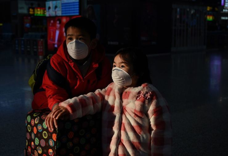 Children wearing protective facemasks look on at the usually full Hongqioa train station in Shanghai on February 5, 2020. AFP-Yonhap