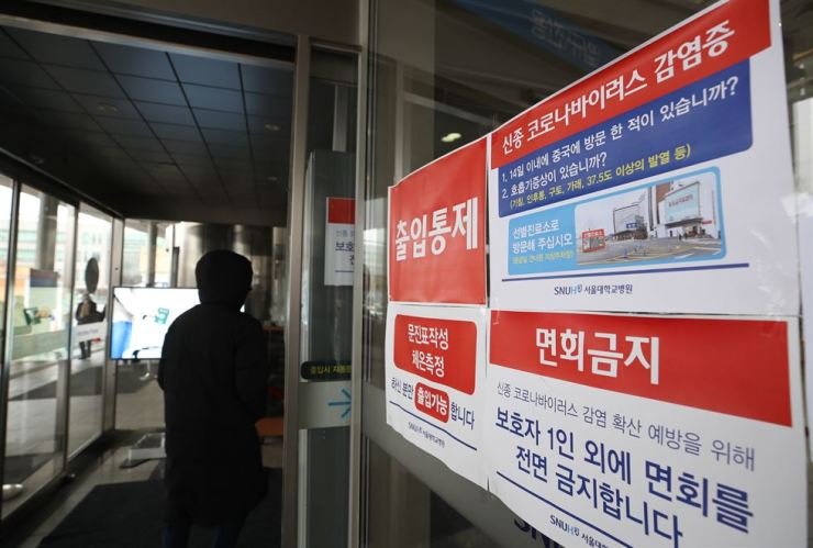 A notice placed at an entrance to Seoul National University Hospital in Seoul, Monday, warns of visiting restrictions to prevent the spread of the coronavirus. Yonhap