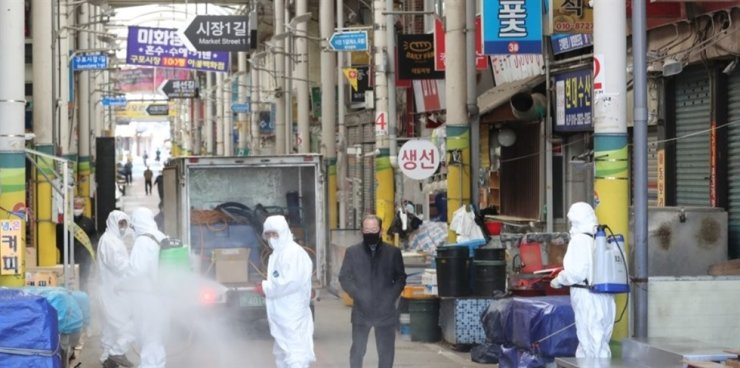 Officials from a vendor association in Busan disinfect Gupo Market in the southern port city to prevent the spread of the coronavirus on Feb. 23. Yonhap