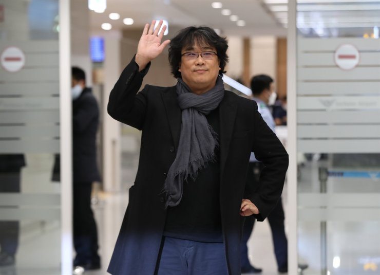 'Parasite' director Bong Joon-ho waves to fans at Incheon International Airport, Sunday, upon returning home after the historic Oscar wins at the 92nd Academy Awards Feb. 10. He said: 'I'm happy that I can now put my mind at ease and return to my work as a creator.' Yonhap