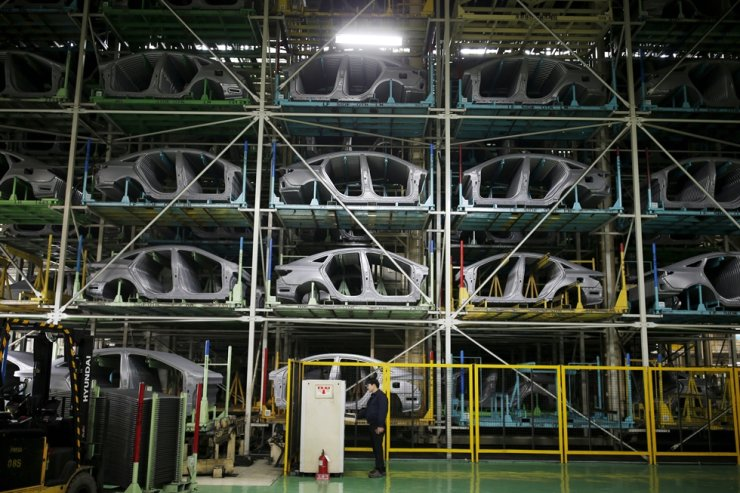 A worker stands in front of parts of Hyundai Motor's sedans at its plant in Asan, Korea, Jan. 27, 2016. Reuters