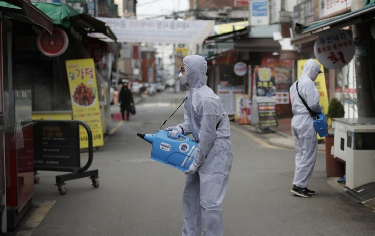 Workers wearing a protective suit spray disinfectant as a precaution against the COVID-19 at a market in Seoul, Wednesday, Feb. 26, 2020. AP