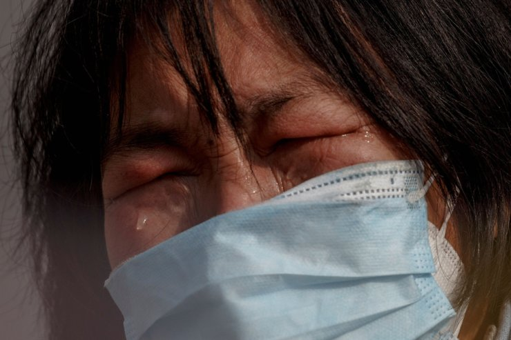 A mother reacts as she pleads with police to allow her daughter to pass a checkpoint for cancer treatment after she arrived from Hubei province at the Jiujiang Yangtze River Bridge in Jiujiang, Jiangxi province, China, as the country is hit by an outbreak of a new coronavirus, February 1, 2020. REUTERS/Thomas Peter