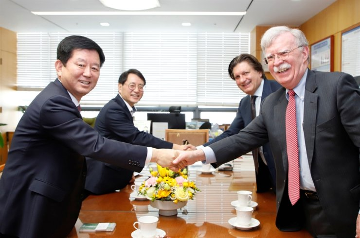 Rhone Group senior adviser John Bolton, right, shakes hands with NongHyup Cooperative Bank President So Seong-mo, left, at the National Agricultural Cooperative Federation (NACF) headquarters in Seoul, Monday. From left are So, NongHyup Cooperative Bank CIO Park Hak-joo, Rhone Group co-founder Robert Agostinelli and Bolton. / Courtesy of NACF
