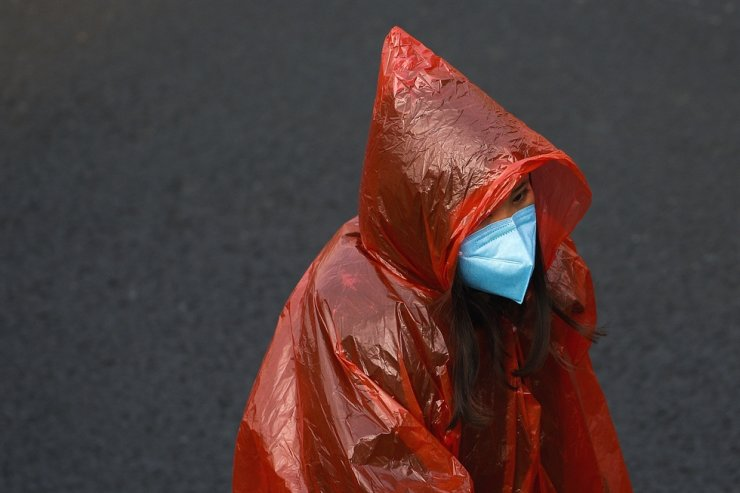 A masked woman in a plastic rain coat walks on a street in Beijing, Tuesday, Feb. 11, 2020. AP