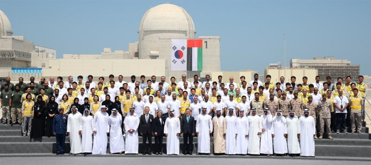 In this March 26, 2018, photo, President Moon Jae-in and Crown Prince of Abu Dhabi Mohammed bin Zayed Al Nahyan stand with government officials and workers of Korea and the United Arab Emirates in front of unit 1 of the Barakah Nuclear Power Plant. Yonhap