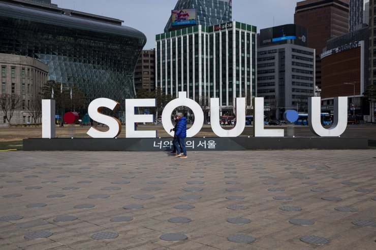People wearing face masks walk past the 'I.Seoul.U' sign near Seoul City Hall in central Seoul, Monday. Korea Times photo by Shim Hyun-chul